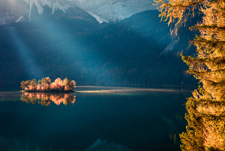 Awesome autumn scene of Eibsee lake. Unbelievable morning view of first sunlight glowing small island on bottom of the Zugspitze peak, Bavaria, Germany, Europe. Beauty of nature concept background.