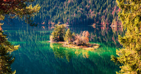 Bright autumn panorama of Eibsee lake. Sunny morning view of small island on bottom of the Zugspitze peak, Bavaria, Germany, Europe. Beauty of nature concept background. 스톡 콘텐츠