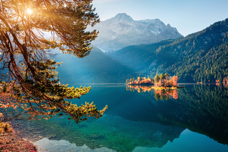 Sunny morning scene of Eibsee lake with Zugspitze mountain range on background. Beautifel autumn sunrise on Bavarian Alps, Germany, Europe. Beauty of nature concept background. Foto de archivo - 116552082
