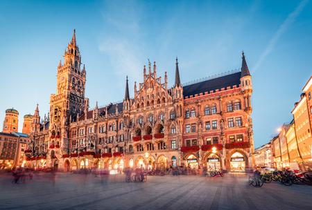 Gran vista nocturna de Marienplatz - plaza del centro de la ciudad y centro de transporte con la imponente iglesia de San Pedro, dos ayuntamientos y un museo del juguete, Munich, Baviera, Alemania, Europa.