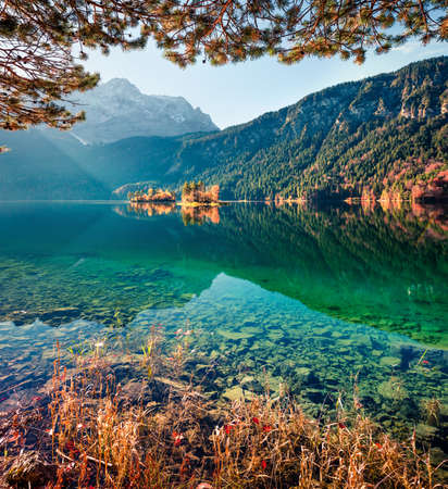 Amazing morning scene of Eibsee lake with Zugspitze mountain range on background. Colorful autumn view of Bavarian Alps, Germany, Europe. Beauty of nature concept background.