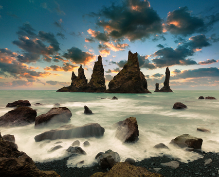 Dramatic seascape of Reynisdrangar cliffs in the Atlantic ocean. Fabulous summer sunset in south Iceland, Vic village location, Europe. Beauty of nature concept background. 스톡 콘텐츠