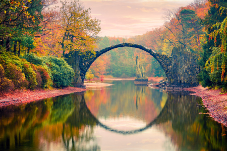 Impressive sunset in Azalea and Rhododendron Park Kromlau, Germany, Europe. Picturesque autumn view of Rakotz Bridge (Rakotzbrucke, Devil's Bridge). Traveling concept background.