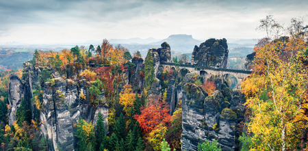 Rainy autumn view of Bastei bridge. Picturesque morning panorama of Saxon Switzerland National Park, Germany, Europe. Beauty of nature concept background.