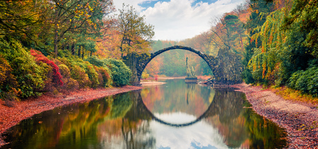 Unbelievable morning scene of Azalea and Rhododendron Park Kromlau, Germany, Europe. Great autumn panorama of Rakotz Bridge (Rakotzbrucke, Devils Bridge). Traveling concept background.