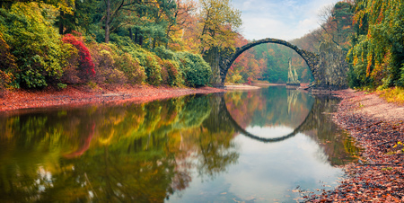 Impressive morning scene of Azalea and Rhododendron Park Kromlau, Germany, Europe. Splendid autumn panorama of Rakotz Bridge (Rakotzbrucke, Devils Bridge). Traveling concept background. 스톡 콘텐츠