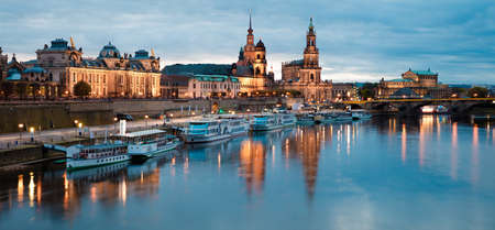 Stunning evennig panorama of Cathedral of the Holy Trinity or Hofkirche, Bruehls Terrace or The Balcony of Europe. Beautiful autumn sunset on Elbe river in Dresden, Saxony, Germany, Europe.