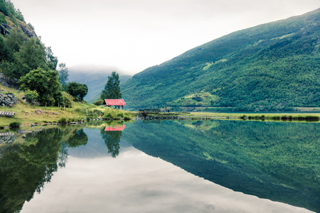 Beautiful summer view of Sognefjorden fjord. Green morning scene of Flom port, Norway. Beauty of nature concept background. Artistic style post processed photo. 스톡 콘텐츠