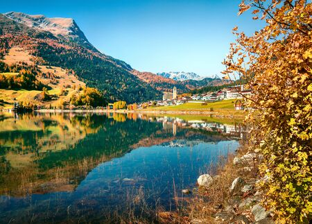 Amazing autumn view of Resia village and lake. Amazing morning scene of Italian Alps, South Tyrol, Italy, Europe. Traveling concept background. Zdjęcie Seryjne