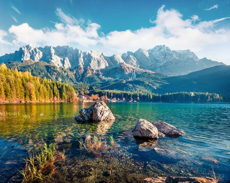 Sunny evening scene of Eibsee lake with Zugspitze mountain range on background. Colorful autumn view of Bavarian Alps, Germany, Europe. Beauty of nature concept background.