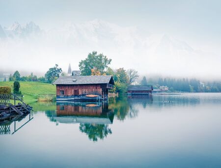 Foggy autumn panorama of Altausseer See lake. Mystical morning view of Altaussee village, district of Liezen in Styria, Austria. Beauty of countryside concept background.