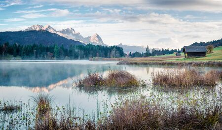 Foggy morning scene of Wagenbruchsee (Geroldsee) lake with Zugspitze mountain range on background. Beautiful autumn view of Bavarian Alps, Germany, Europe.
