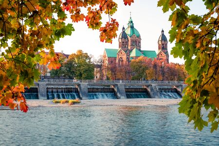 Splendid autumn view of Landmark Protestant St. Lukes Church and Isar river. Bright morning cityscape of Munich, Bavaria, Germany, Europe. Traveling concept background. Zdjęcie Seryjne