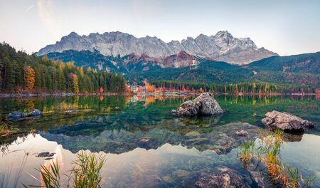 Gorgeous morning scene of Eibsee lake with Zugspitze mountain range on background. Colorful autumn view of Bavarian Alps, Germany, Europe. Beauty of nature concept background.