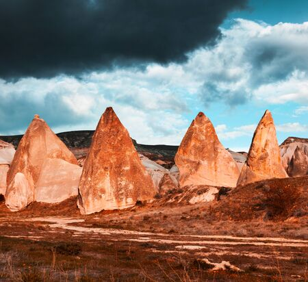 Dramatic spring scene of Cappadocia. Picturesque morning view of of Red Rose valley in April. Cavusin village located, district of Nevsehir, Turkey, Asia. Infrared filter toned. Фото со стока