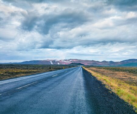 Empty asphalt road with colorful cloudy sky. Beautiful outdoor scenery in the Hverarond geothermal valley, Iceland, Europe. Travel concept background. Banco de Imagens
