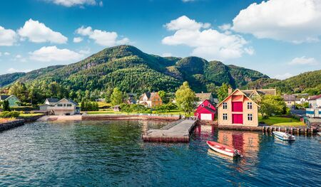 Picturesque summer view of typical Norwegian village Jondal, on the shore of fjord. Sunny morning panorama of countryside, Norway, Europe. Traveling concept background.