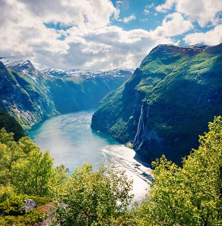 Sunny summer scene of Sunnylvsfjorden fjord, Geiranger village location, western Norway. Aerial view of famous Seven Sisters waterfalls. Beauty of nature concept background.