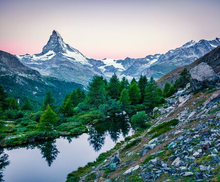 Fantastic summer sunrise on Grindjisee lake. Picturesque morning view of  Matterhorn (Monte Cervino, Mont Cervin) peak, Swiss Alps, Zermatt location, Switzerland, Europe. Beauty of nature concept back