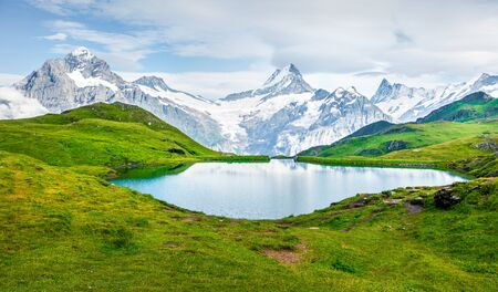 Splendid summer view of the Bachalpsee lake with Schreckhorn peak on background. Colorful morning scene of Swiss Bernese Alps, Switzerland, Europe. Beauty of nature concept background.