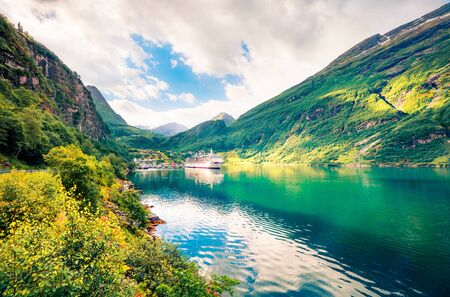 Sunny summer scene of Geiranger port, western Norway. Splendid morning view of Sunnylvsfjorden fjord. Traveling concept background. Artistic style post processed photo.