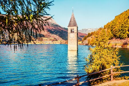 Sunny autumn view of Tower of sunken church in Resia lake. Amazing morning scene of Italian Alps, South Tyrol, Italy, Europe. Traveling concept background. Stockfoto