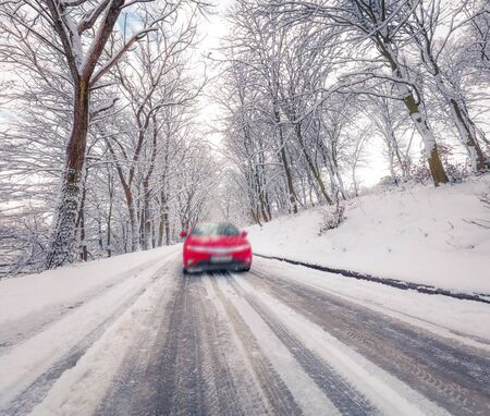 Driving a car on the road in winter forest with snow covered trees. Snowy outdoor scene. Traveling concept background.