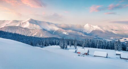 Frosty winter sunrise in Carpathian mountains with snow covered fir trees. Dreamy outdoor panorama, Happy New Year celebration concept. Artistic style post processed photo. Orton Effect. Reklamní fotografie