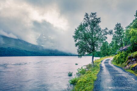 Gloomy summer view of the Innerdalsvatna lake. Misty morning scene in Norway, Europe. Beauty of nature concept background. Artistic style post processed photo.