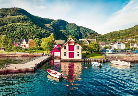 Attractive summer view of typical Norwegian village Jondal, on the shore of fjord. Sunny morning panorama of countryside, Norway, Europe. Traveling concept background.