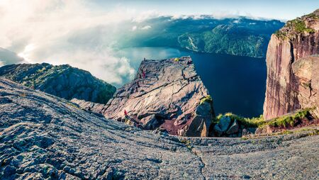 Aerial morning view of popular Norwegian attraction Preikestolen. Foggy summer scene of the Lysefjorden fjord, located in the Ryfylke area in southwestern Norway. Beauty of nature concept background. Stok Fotoğraf