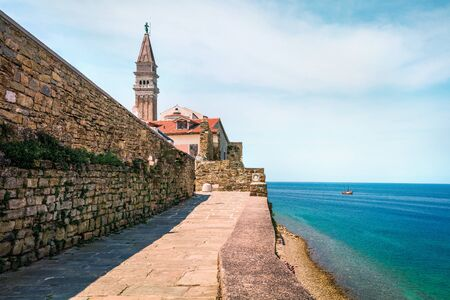 Sunny summer view of St. Georges Parish Church in Piran town. Splendid spring morning on Adriatic Sea. Beautiful cityscape of Slovenia, Europe. Traveling concept background.