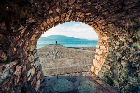 Photographer takes picture from quay in Nafpaktos port. Beautiful morning scene of Gulf of Corinth, Greece, Europe. Traveling concept background.