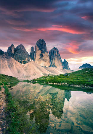 Dramatic summer sunrise with Rienza - Ursprung lake in National Park Tre Cime di Lavaredo. Great morning view of Dolomite Alps, South Tyrol, Auronzo Location, Italy, Europe. Beauty of nature concept background.