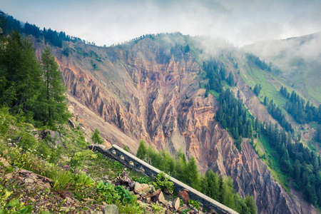 Ruins of old mountain road in dolomite Alps. Impressive morning scene in Italy. Misty summer landscape ot the high mountains. Traveling concept background.