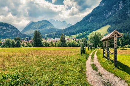 Great summer view of Triglav mountain range and  Gozd Martuljek village. Sunny morning scene of Julian Alps, Slovenia, Europe.