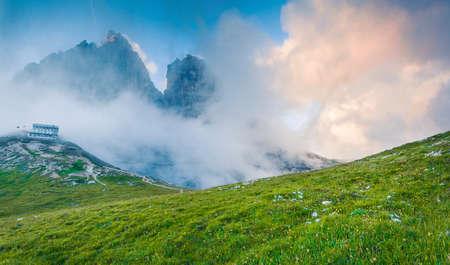 Misty summer view of Three Peaks of Lavaredo and Rifugio Auronzo. Picturesque morning scene of Tre Cime De Lavadero national park, Dolomite Alps, Italy, Europe. Orton Effect.