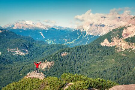 Climber standing on the top of cliff and raising his hands up. Fantastic summer view of Cristallo mountain range in the morning mist, Dolomite Alps, Italy, Europe. Traveling concept background.