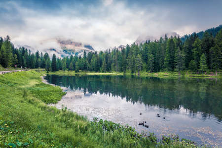 Great summer scene of Antorno lake with Tre Cime di Lavaredo (Drei Zinnen) mount in the morning mist. Colorful autumn view of Dolomite Alps, Italy, Europe. Beauty of nature concept background.