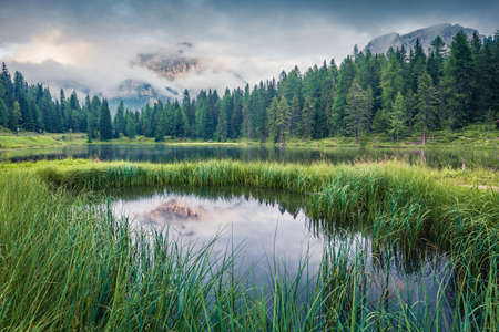Fantastic summer scene of Antorno lake with Tre Cime di Lavaredo (Drei Zinnen) mount in the morning mist. Misty autumn view of Dolomite Alps, Italy, Europe. Beauty of nature concept background.