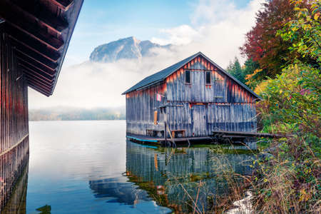 Spectacular autumn scene of Altausseer See lake with Trisselwand peak on background. Foggy morning view of Altaussee village, district of Liezen in Styria, Austria. Orton Effect.