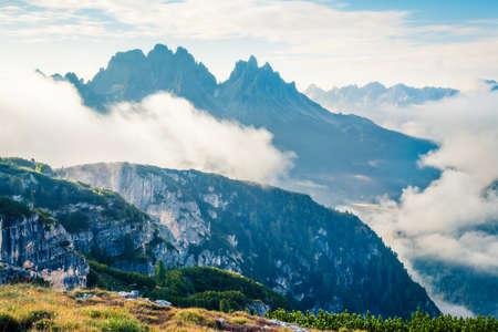 Foggy summer view of Gruppo Del Cristallo mountain range in Tre Cime Di Lavaredo national park. Sunny morning scene of Dolomite Alps, Italy, Europe. Beauty of nature concept background. Orton Effect.