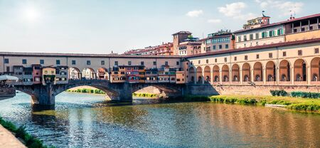 Beautiful medieval arched river bridge with Roman origins - Ponte Vecchio over Arno river. Bright spring morning panorama of Florence, Italy, Europe. Traveling concept background.