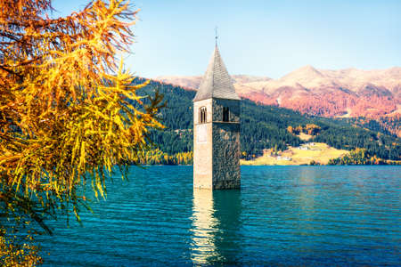 Captivating autumn view of  bell tower of Curon Venosta church rising out of the waters lake of Resia, Graun im Vinschgau village, Trentino-Alto Adige region of Italy, Europe. Orton Effect.
