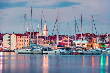 Illuminated cityscape of old fishing town Isola. Great spring seascape of Adriatic Sea. Beautiful evening panorama of Slovenia, Europe. Traveling concept background. Orton Effect.
