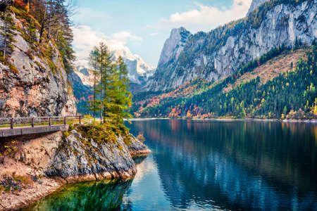 Attractive autumn scene of Vorderer ( Gosausee ) lake with Dachstein glacieron background. Amazing morning view of Austrian Alps, Upper Austria, Europe. Traveling concept background.