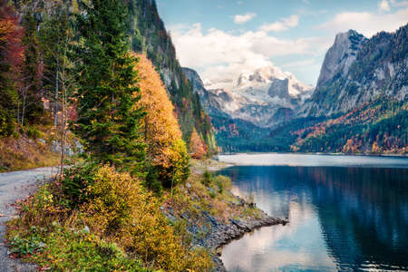 Amazing autumn scene of Vorderer ( Gosausee ) lake with Dachstein glacieron background. Majestic morning view of Austrian Alps, Upper Austria, Europe. Traveling concept background.