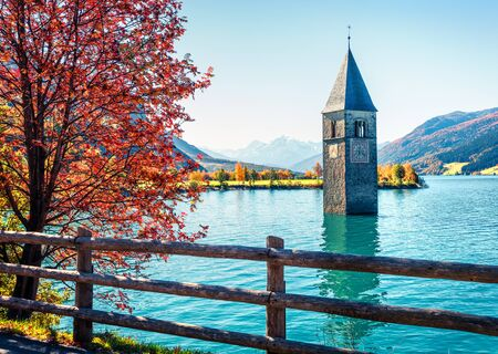 Attractive autumn view of Tower of sunken church in Resia lake. Amazing morning scene of Italian Alps, South Tyrol, Italy, Europe. Traveling concept background.