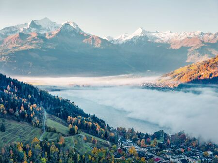 Gorgeous view of Zell lake in the morning mist with Grossglockner peak on background. Foggy autumn sunrise in Austria, Europe, Zell am See town. Stok Fotoğraf