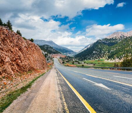 Empty asphalt road with dramatic cloudy sky. Beautiful outdoor scene of  Turkey, Asia. Image of travel concept background.